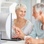 A senior man teaching a senior woman how to use the computer